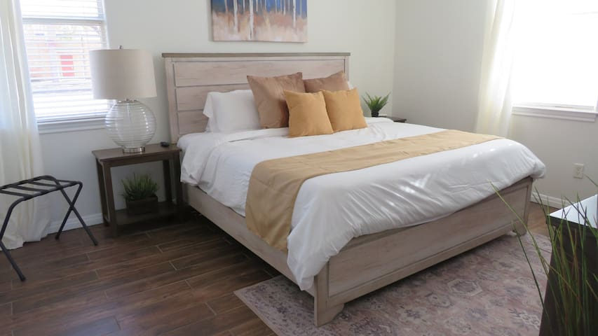 Downstairs master bedroom with king bed, walk in closet and en suite private bathroom featuring a walk in shower