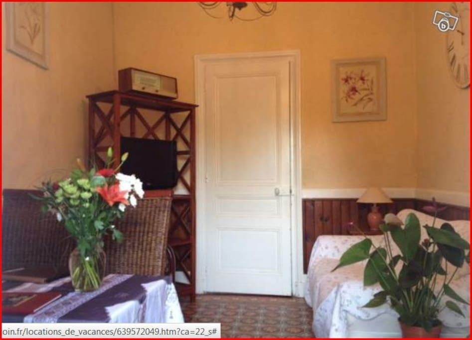 Le salon avec télé écran plat, box télé et canapé confortable