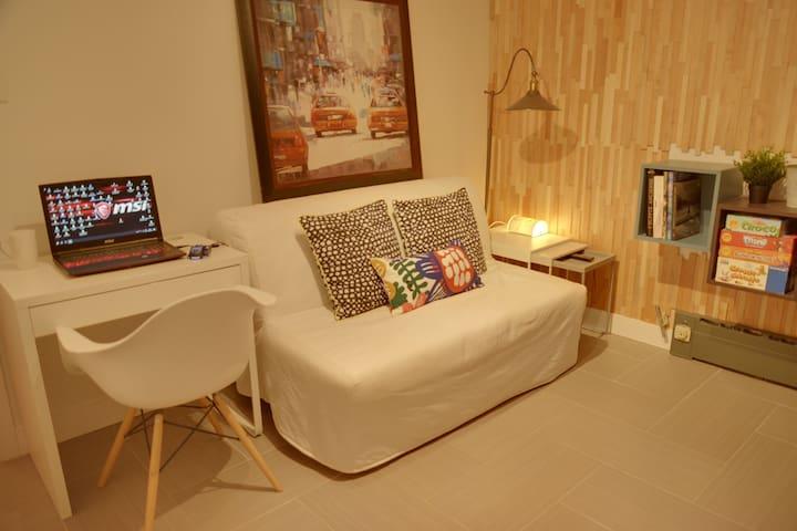 Salon avec divan-lit, téléviseur et espace bureau. Cette pièce est l'endroit où vous entré directement.