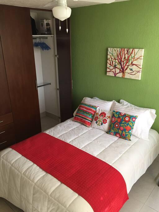 Una cama matrimonial, ventilador de techo y closet disponible con ganchos