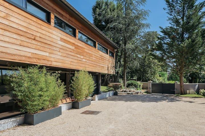 A gauche façade ouest et au fond l'entrée avec sur la gauche un espace pic-nique entouré de verdure - La maison de Karen chocolat , à Limonest dans le Rhône