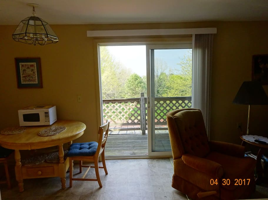 Dining room/livingroom with deck in background. Views of city of Rochester from deck.