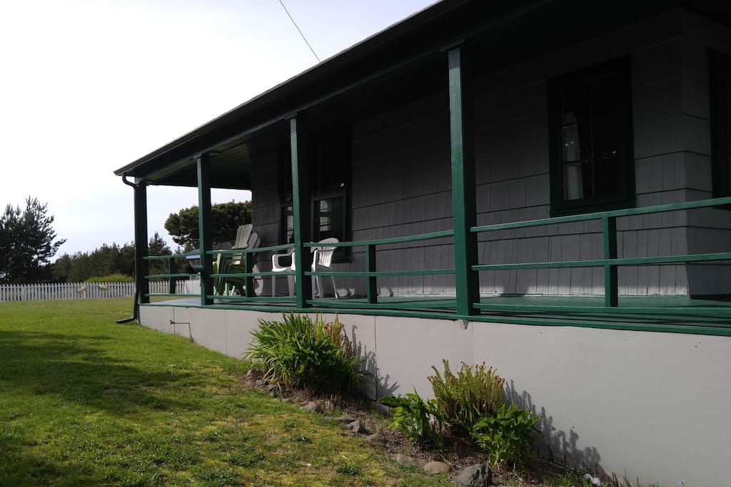 Showing the large picket-fenced garden and wrap-around porches of the cottage.