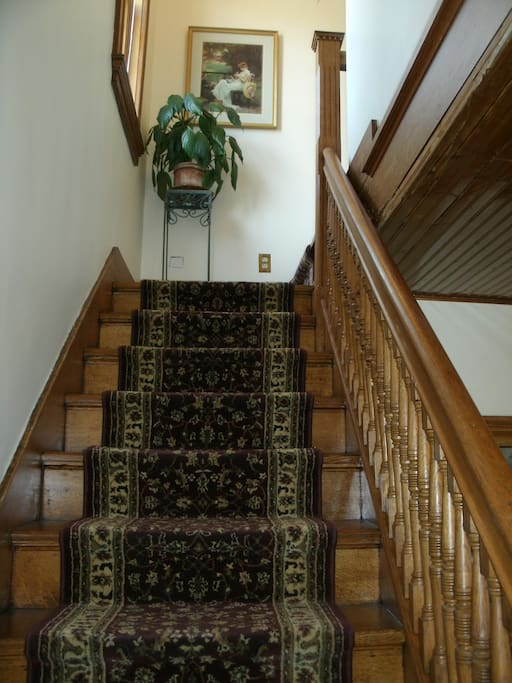 Carpeted oak staircase leads to the apartment.