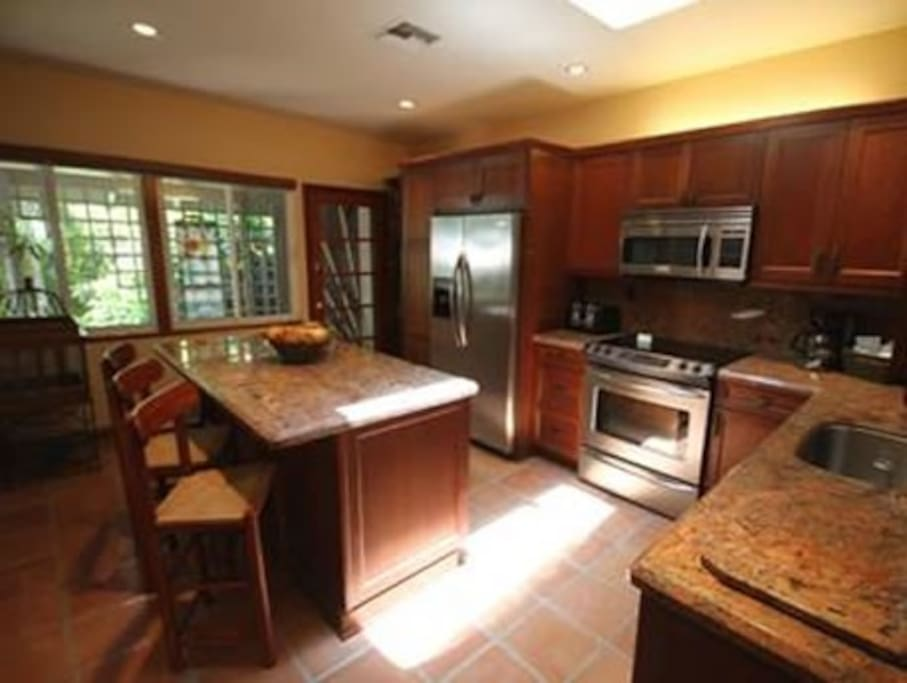 Kitchen with center island and 3 chairs.
