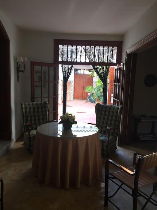 Foto desde la entrada de casa, a la derecha se ve un espacio abierto con un mueble bar y mesa de juegos y a la izquierda la sala de estar y enfrente tenemos el patio