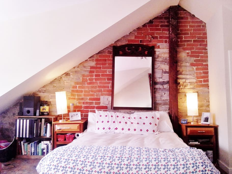 Your bed. Comfortable, warm, Queen-sized. Open limestone/brick wall.