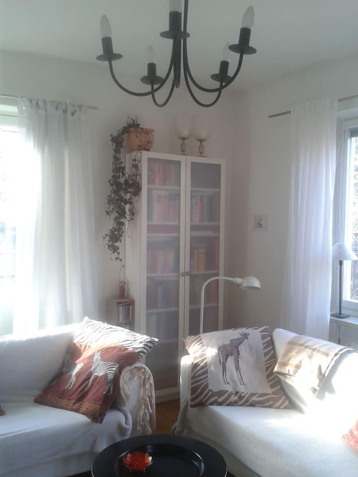 Mysigt vardagsrum med 2 soffor, matbord och stolar, balkong