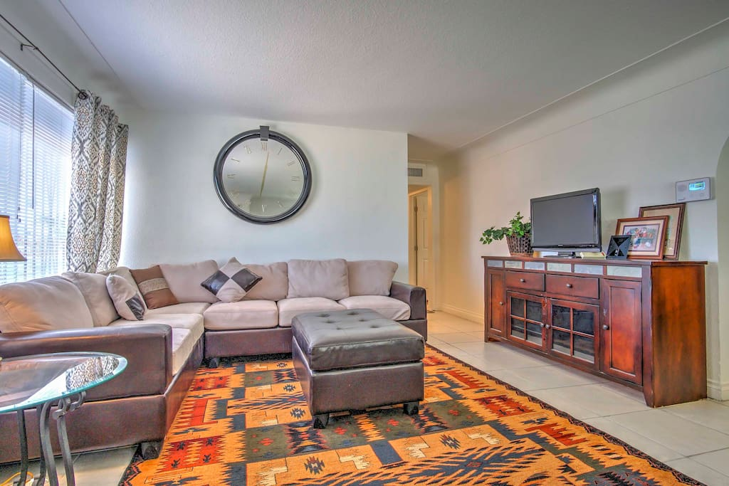 The living room features a comfortable wrap-around couch and a TV with local HD channels.