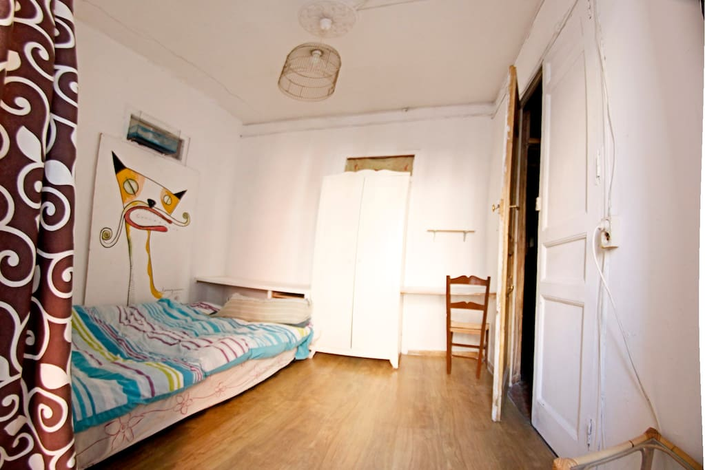 the cat room with double bed, balcony and a large window.