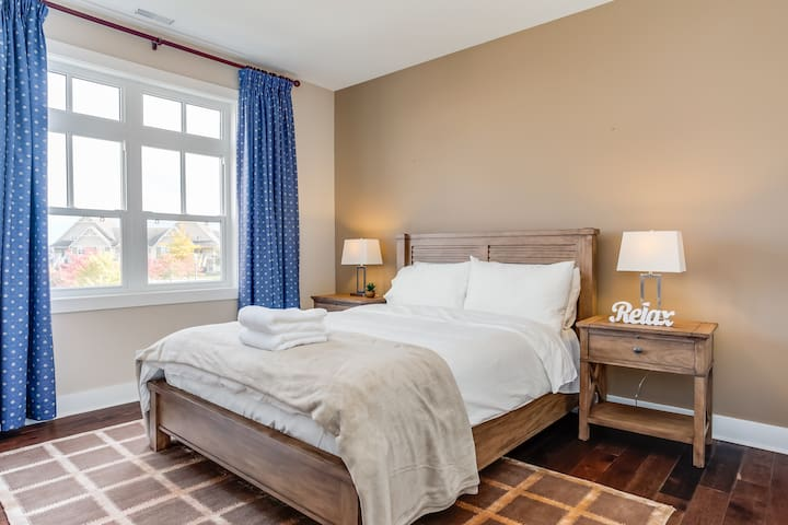 This spacious guest bedroom has a comfortable queen bed.