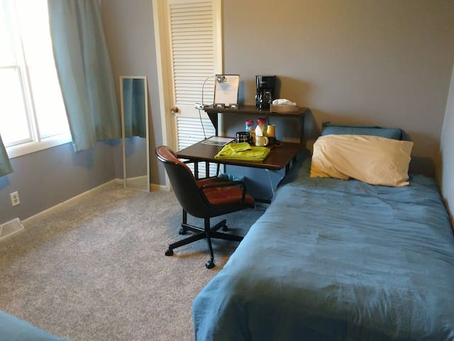 Bed #2. Natural lighting during the day. Desk and chair, towels, washcloths, coffee, full length mirror. Bathroom is across the hallway.