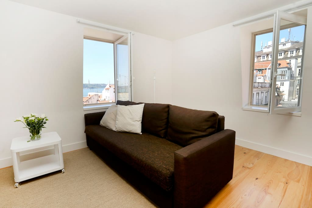 a sofa-bed in the living room; Windows with view to the historic center roofs and the Tagus River,  plenty of natural light