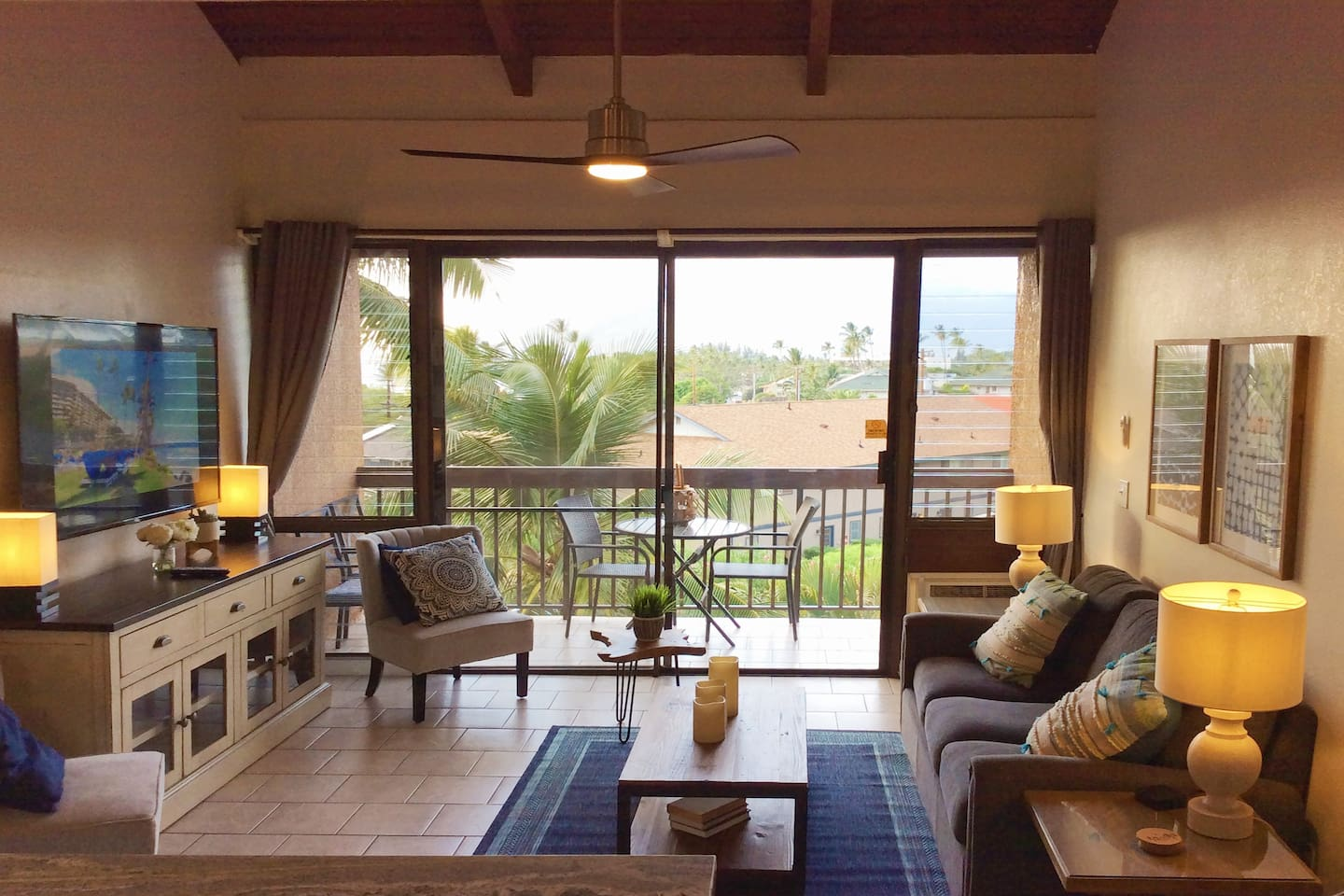 Living area of the condo with with view from the lanai, features air conditioner, ceiling fan, sleeper sofa, comfy chairs, and large flat-screen TV.