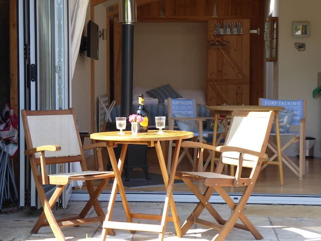 The Patio area with dining area leading out from the open bifold doors from the Sea Breeze Beach House