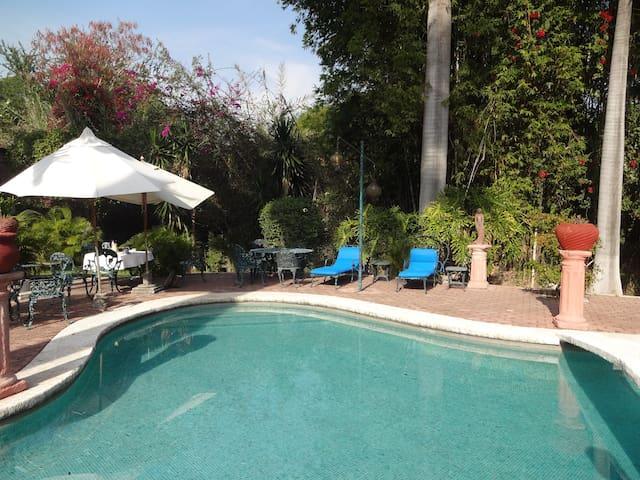Amplio jardín con alberca que tiene camastros, sillas para descansar y pasar ricas vacaciones
