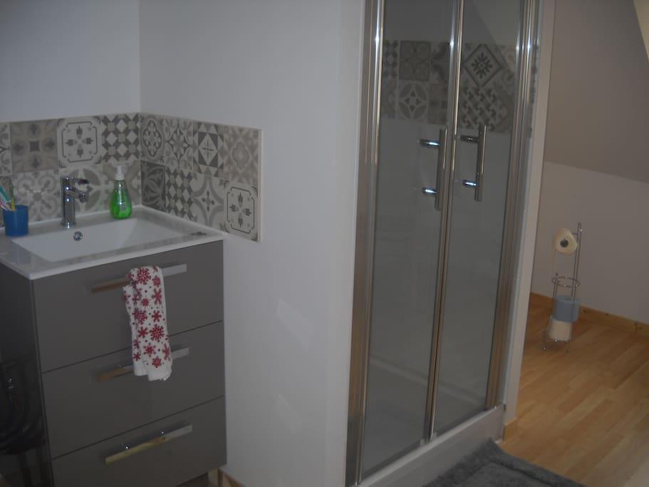 Salle de bain avec toilette commune à plusieurs chambres.