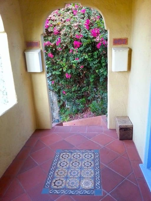 Enter through a Spanish tiled stairway drenched in bougainvillea