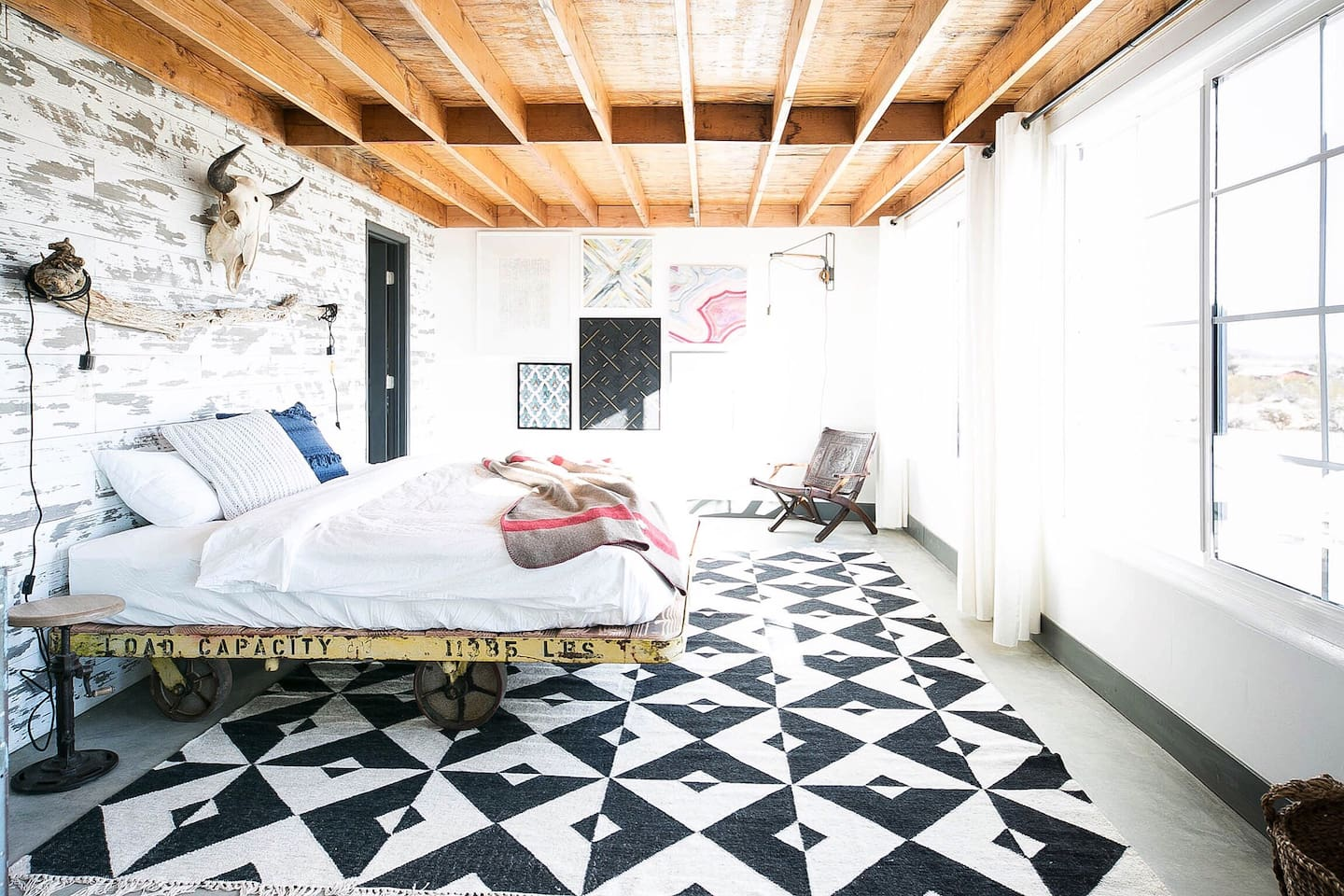 Tow Master Bedroom,This Is The First One,An Industral Cart Converted To A King Size Bed,With a Handmade Black And White Rug.