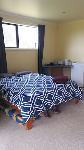 Comfortable queen bed and kitchenette in background