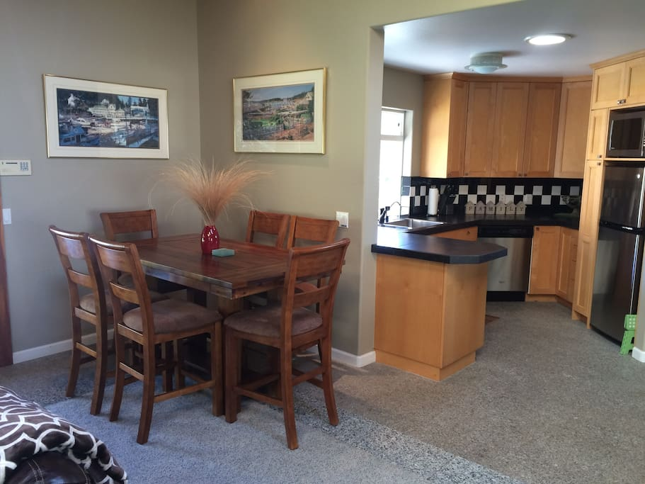 Dining table and kitchen area.  Seating for 8. Refrigerator with ice maker. Induction cook tops, cookware, knives, microwave, crock pot, coffee makers, blender, dishes, silverware, and serving dishes and serving utensils.  Everything needed to easily prepare meals.