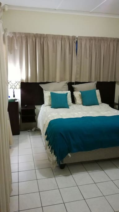 Spacious double room with toilet and small basin, door to patio and braai