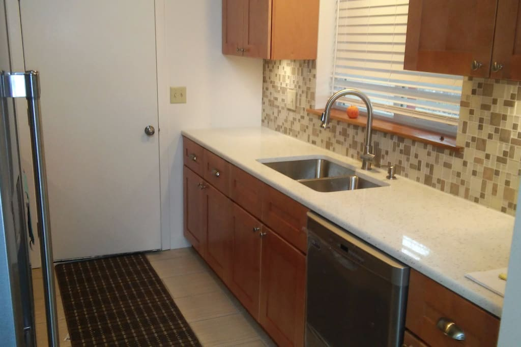 Full high end kitchen with stove, microwave & dishes
