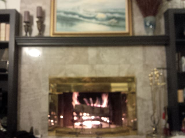 For winter enjoyment: amazing marble-faced wood burning fireplace.