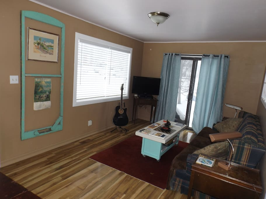Spacious & bright with a full size couch and dining table. Patio doors onto deck, DVD player with many titles & series. Atari classic controller with 24 games, karaoke Bluetooth speaker with two mics, & guitar. 40 inch Wi-Fi Smart TV.