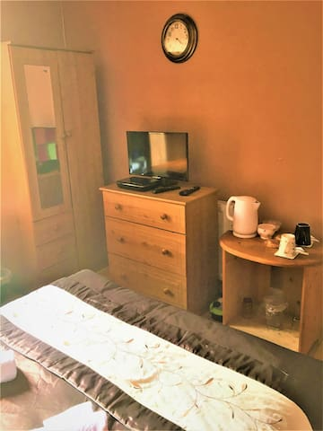 Wardrobe with hangers to hang clothes and chest of drawer to put clothes. Help yourself to hot or cold drink from the side table. Television with national & international channels.