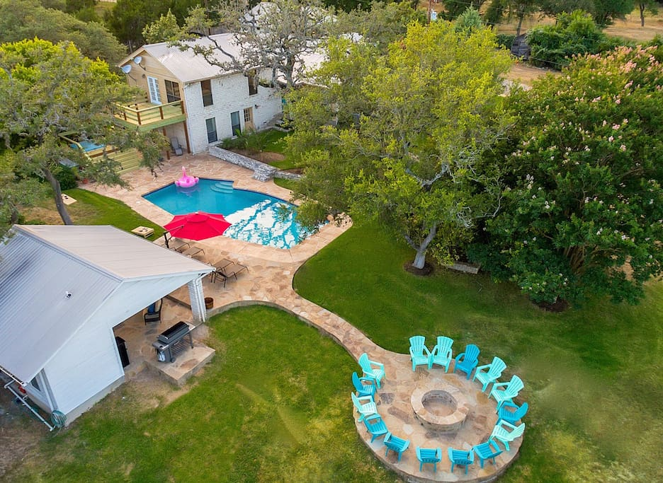 This drone shot provides a great perspective on how much space you have all around the pool for relaxing and enjoying yourselves.  The pool house has the biggest grill Weber manufactures (6 burner) which provides ample room for all of your grilling needs, a 65in high definition TV with the complete DirecTV satellite programming, a wet bar, refrigerator/freezer, a blender for mixing drinks and a very large 1/2 bath.   You can also see our 10,000 gallon rain water collection tank which helps us conserve the water from our aquifers.  We provide firewood for building a fire in the fire pit. Its always fun sitting around telling stories and roasting s'mores.