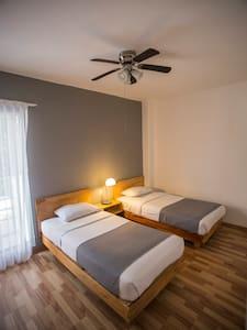 Habitación privada Hostal Doble con 2 camas individuales para 2 personas, regadera y lavabo DENTRO de la habitación, TV con cable, aire acondicionado, ventilador, closet, escritorio y cortinas black out. W/C es compartido.