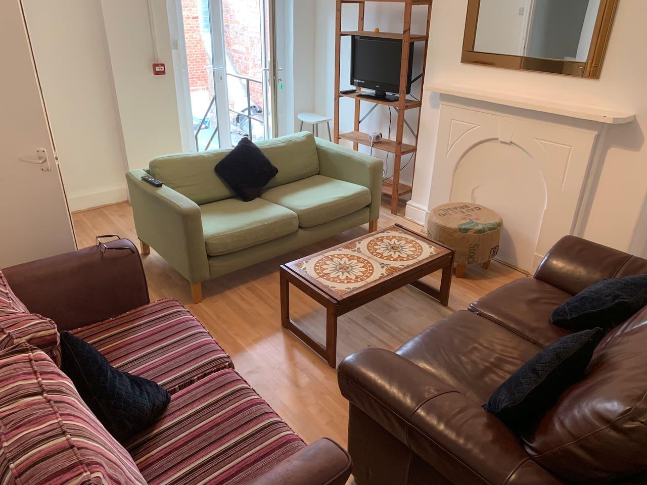 Living room has 3 sofas.