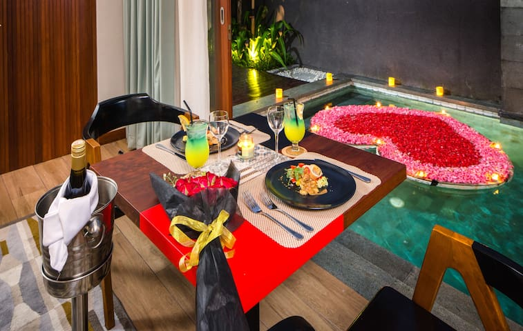 Romantic dinner setup at living room with floating love at pool