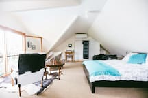 Loft bedroom and sitting room with raked ceiling, shelf and hanging space, and an abundance of natural light