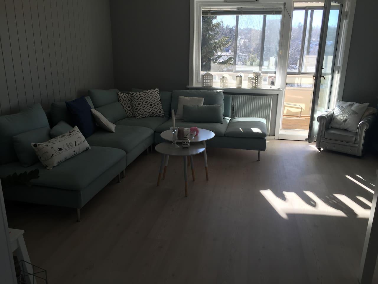 stue med stor hjørne sofa. og utgang til balkong