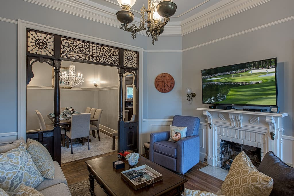 Living room with large TV opens to formal dining room.