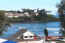 View from pool, of people paddle boarding agnes siding in Kalapaki Bay.