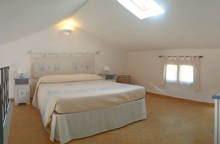 Loft with comfortable double bed. Bajaur, headboard and bed covers are of Sardinian handicrafts.