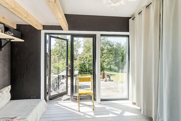 Gæsteværelset med udgang til haven. Sovesofa med to madresser (80x200) og en hems over med plads til 2 personer (140x200).