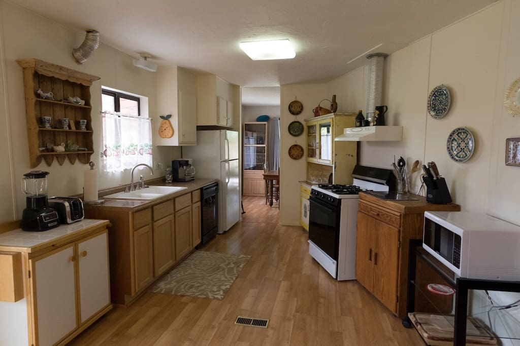 Fully-equipped kitchen with gas stove, microwave, coffee pot, toaster.