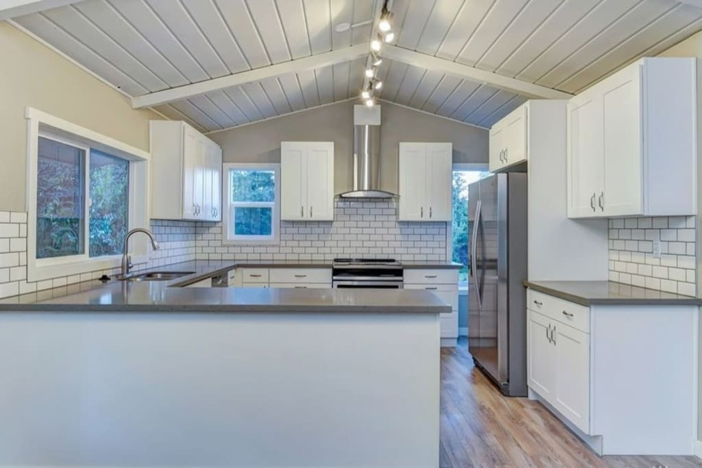 Chef's kitchen with stainless appliances and quartz counters.