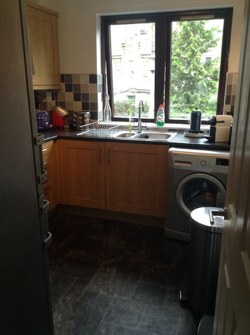 Spacious kitchen with access to fridge, washing machine and other utilities.