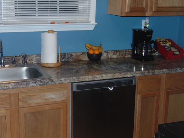 Full kitchen with dishwasher, stove top, oven, and full-sized refrigerator.