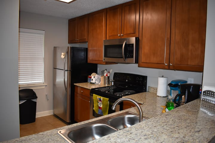 Fully functioning kitchen with a washer & dryer tucked around the corner.