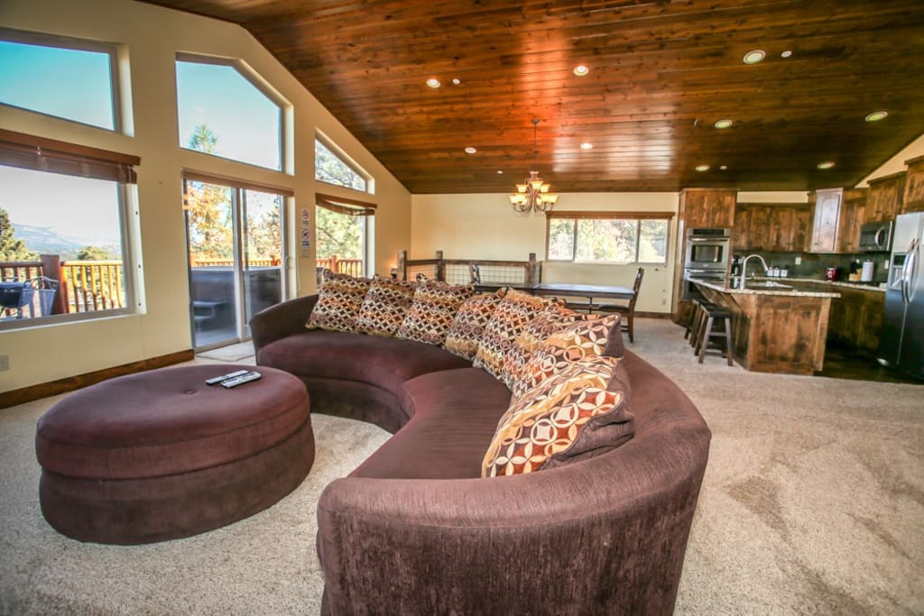 This room features gorgeous views of all of Big Bear! You can see the alpine slide, Big Bear Blvd, the lake, and the mountains! This room is also great for large groups. A beautiful, modern kitchen and bar can been seen in the background.