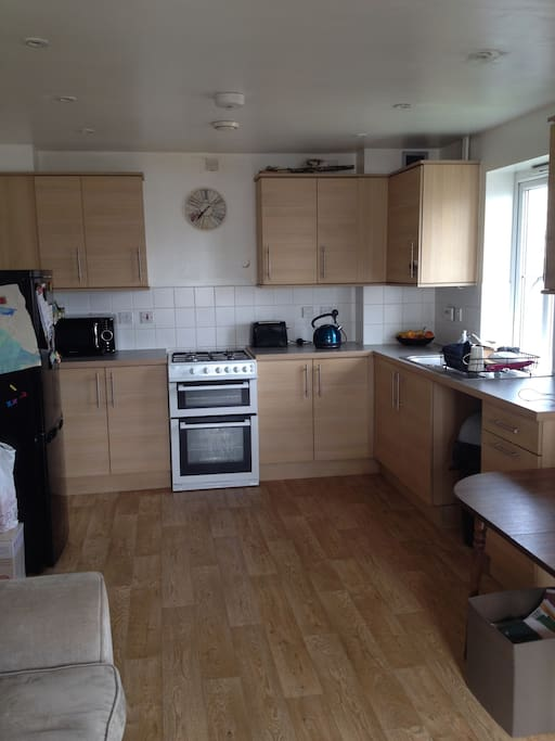Kitchen with, refrigerator, dishwasher,microwave, kettle, cooker, toaster.