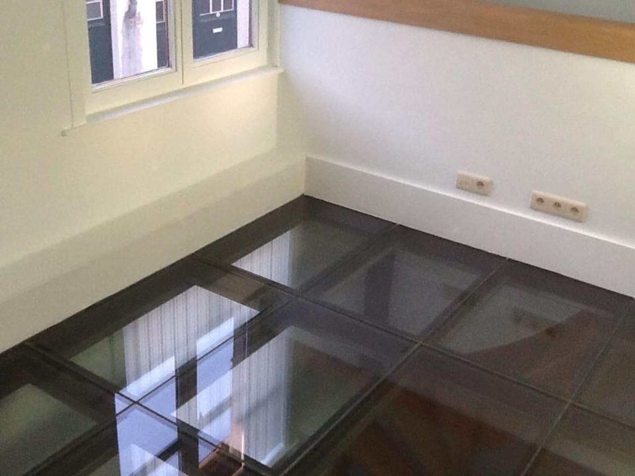 logeerkamer , glazenvloer, een half open muur aan de traphal