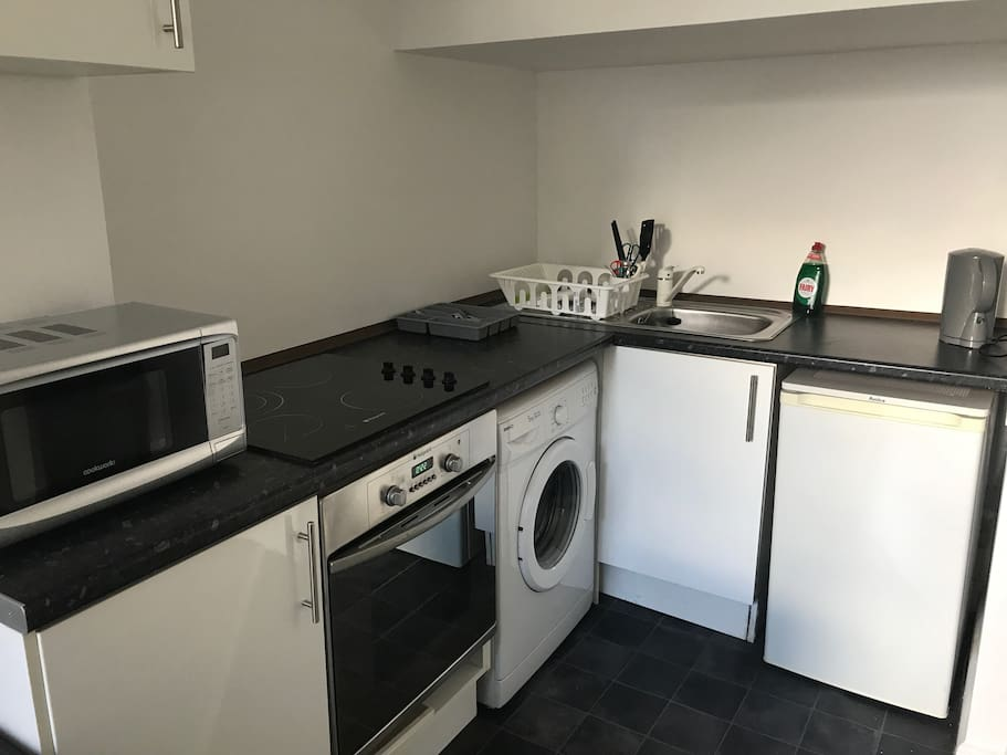 Fully equipped kitchen with microwave, hob, oven, fridge with freezer compartment and washing machine
