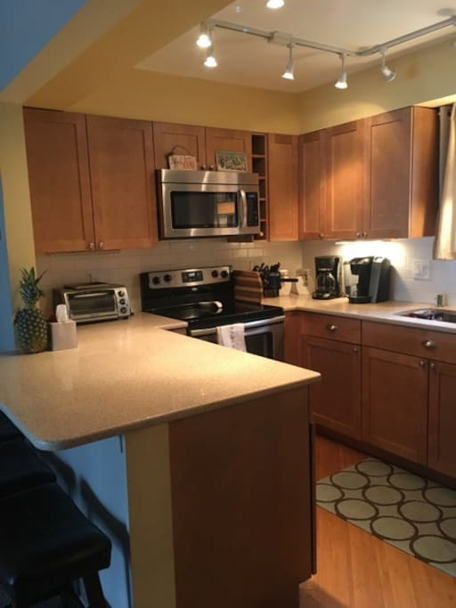 Modern kitchen with electric range, toaster oven, Keurig, coffee maker and griddle for pancakes in the morning